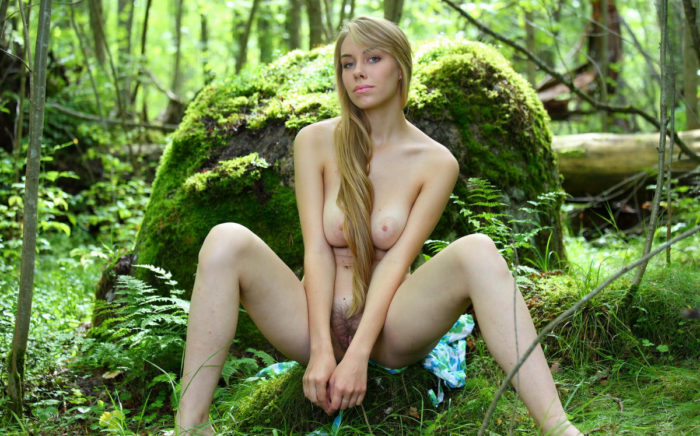 Tall blonde with beautiful face in the forest
