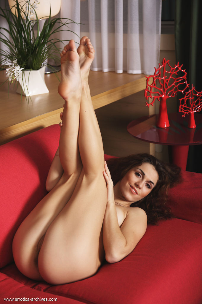 Eva Kane flaunts her sexy, slender body and sweet pussy as she sensually poses on the couch.
