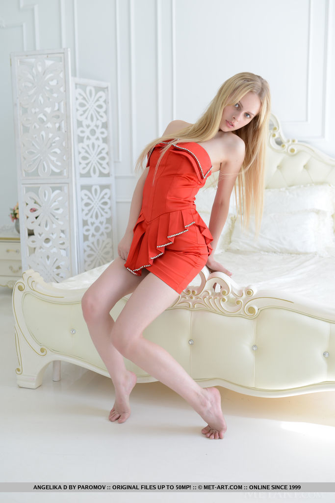 Angelika D takess off her red orange dress and sprawls naked on top of the bed