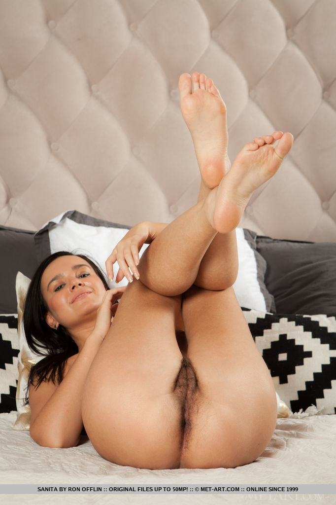 Sanita shows off her large breasts, meaty ass and unshaven pussy as she poses on the bed.