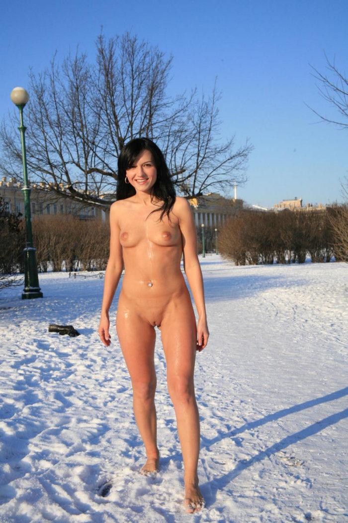 Bare brunette at winter public park