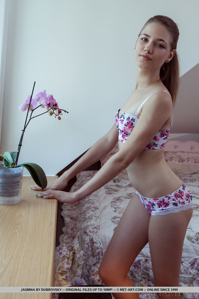Jasmina strisp her flowery lingerie baring her slender body with smooth, wet   pussy as she poses on the bed.