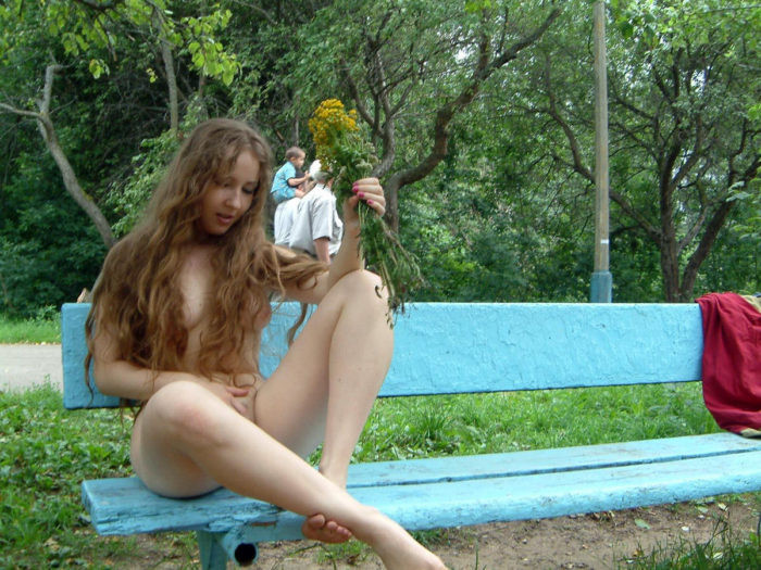 Long-haired naked teen sitting on a park bench