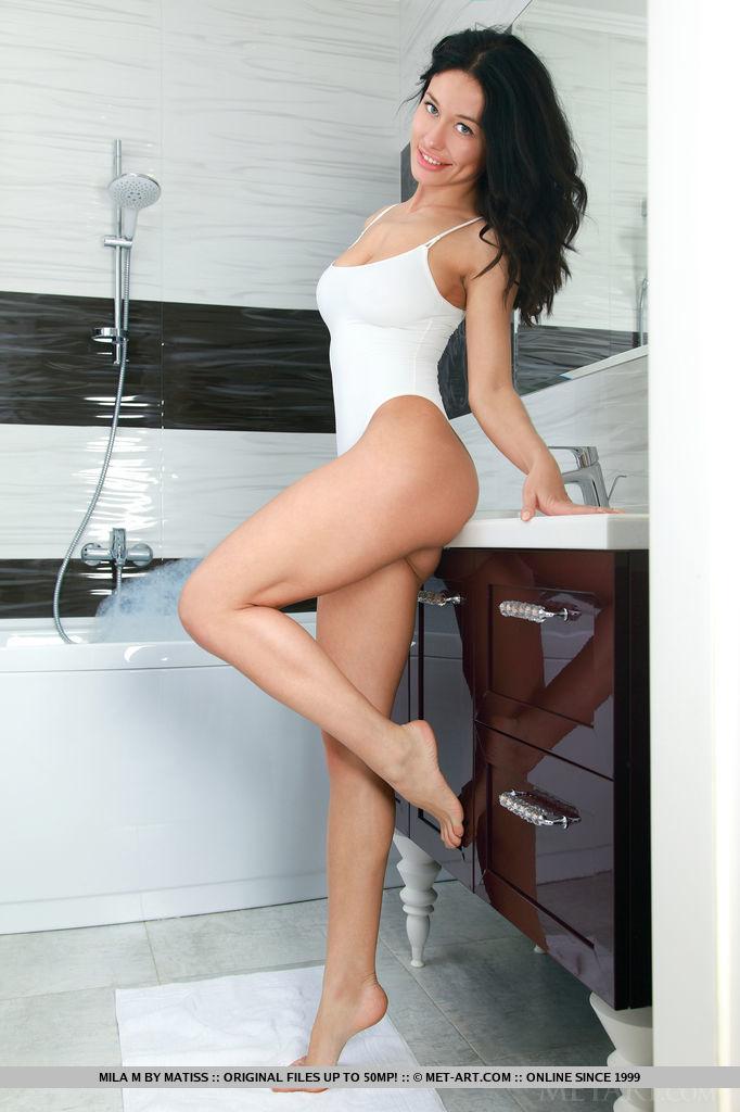Mila M strips her one-piece bikini as she bares her wet, gorgeous body into the bathtub.