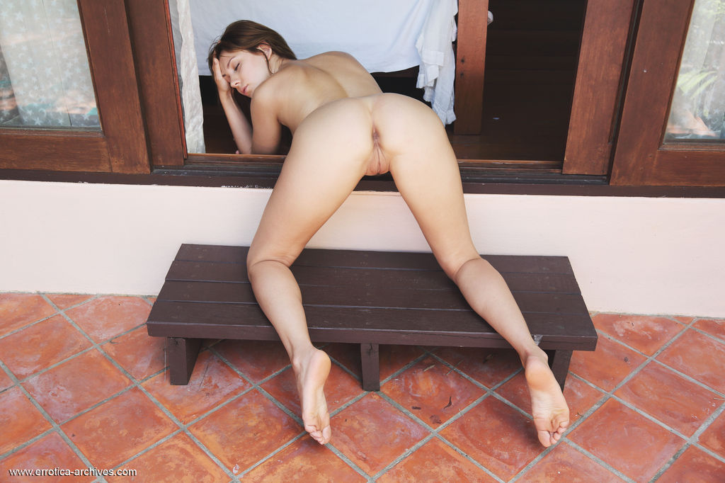 Oliana erotically poses by the door baring her delectable body and sweey pussy.