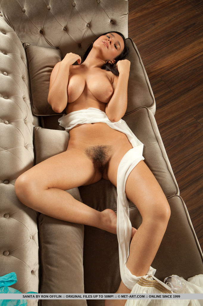 Sanita bares her large breas, curvy body and unshaven pussy as she sensually poses on   the couch.
