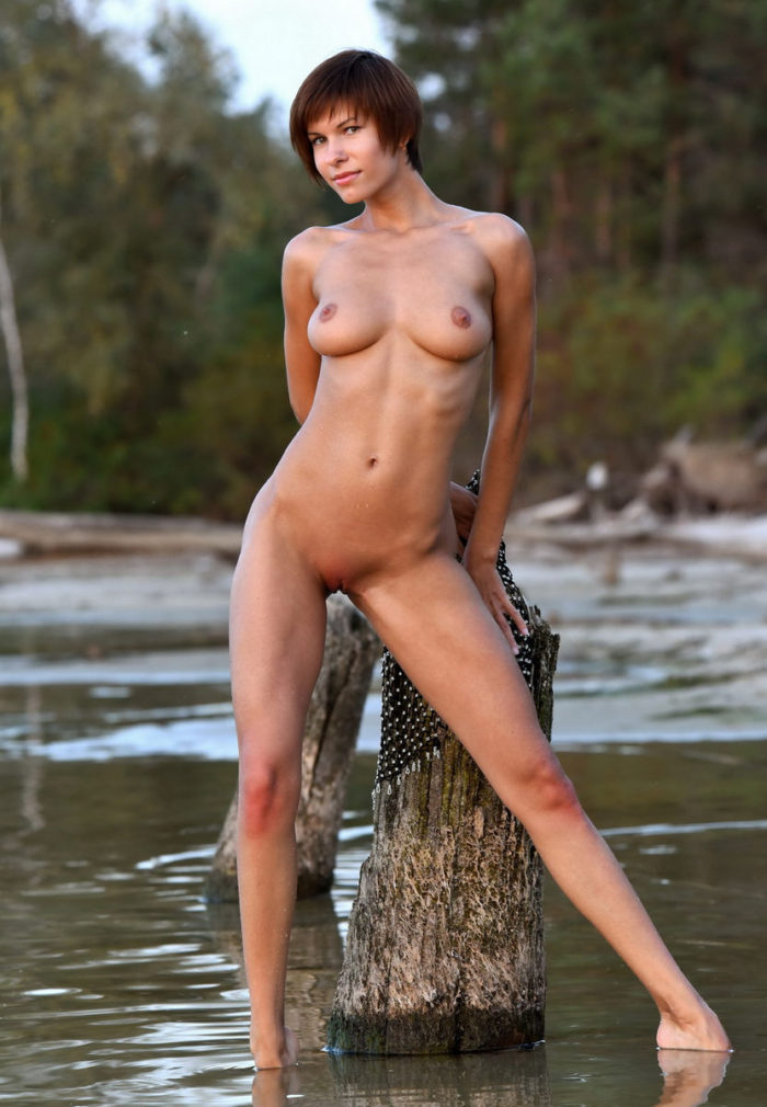Short-haired babe Suzanna A with perfect body posing at river