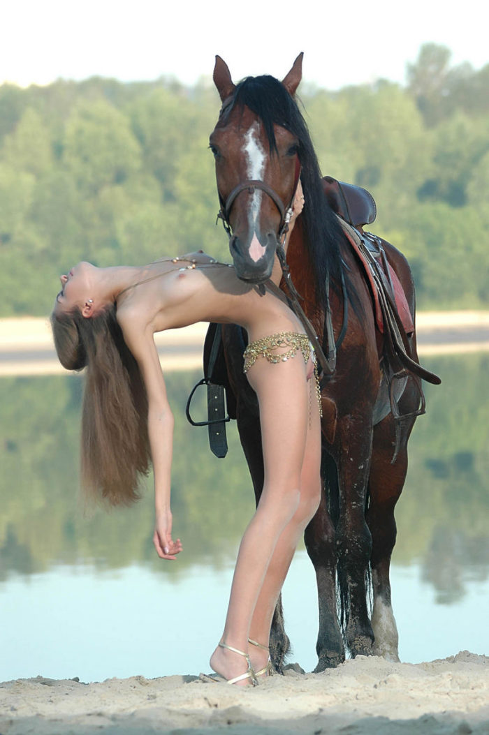 Young Alya with skinny body posing with horses outdoors