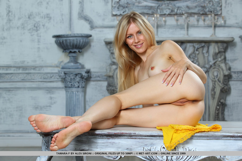 A confident Tamara F poses naked in front of the camera with a cheerful smile in her pretty face