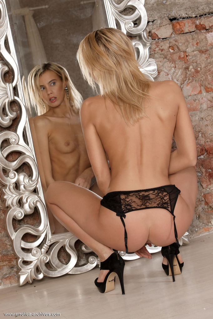 Brigitte D flaunts her petite body with small tits as she poses by the mirror.