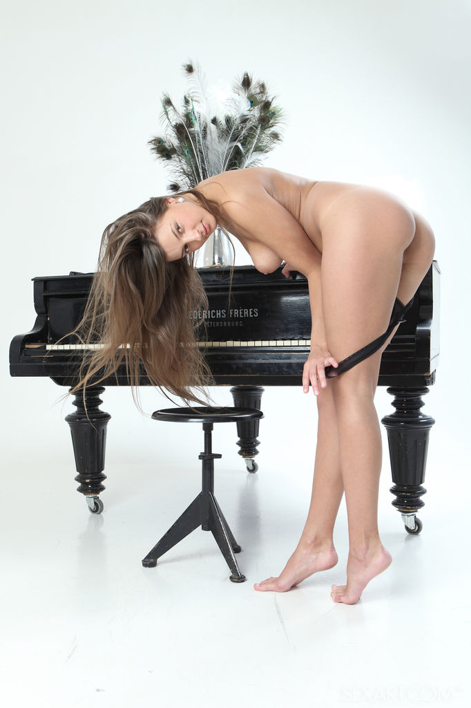 Petite goddess Melena A strips off her sheer black lingerie and starts masturbating on top of the piano