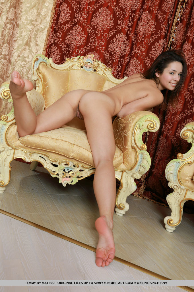 Emmy bares her nubile body with puffy tits and delectable pussy as she poses on the chair.