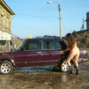 Girl with no clother washes taxi car outdoors