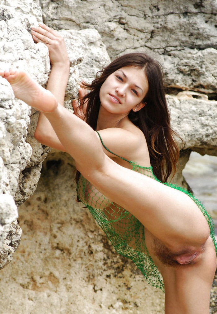 Gorgeous Sofi A in fishnet dress on sea rocks