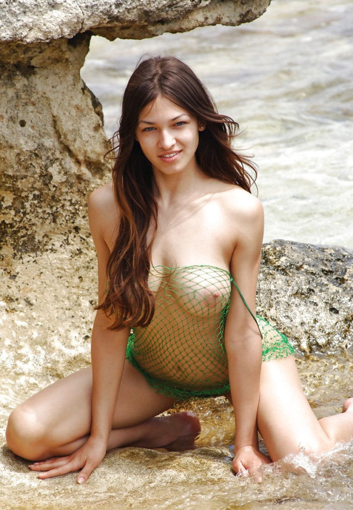 Gorgeous Sofi A in fishnet dress on sea rocks