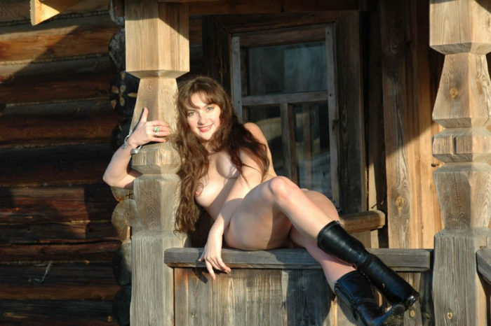 Long-haired Angelika posing naked by an old house