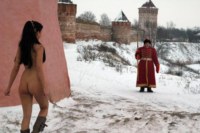 Naked brunette meets warrior with halberd