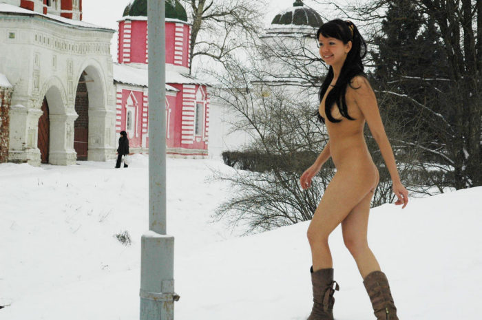 Nude brunette plays with snow in city