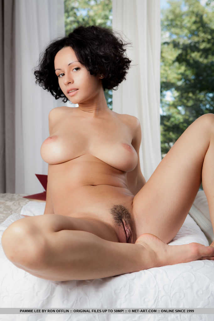 Pammie Lee shows off her curvy body with large breasts as she sensually poses on the bed.
