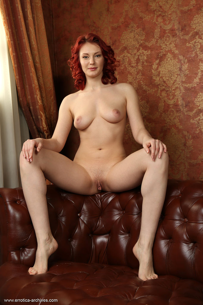 Redhead Rachel Fox flaunts her gorgeous body with pink nipples and delectable pussy as she poses on the   couch.