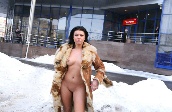 Sexy brunette with nice natural body walks at winter city
