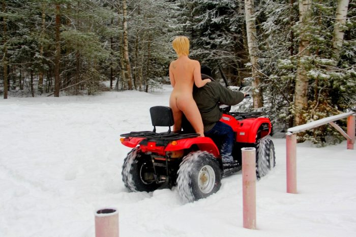 Short-haired blonde rides ATV at winter forest