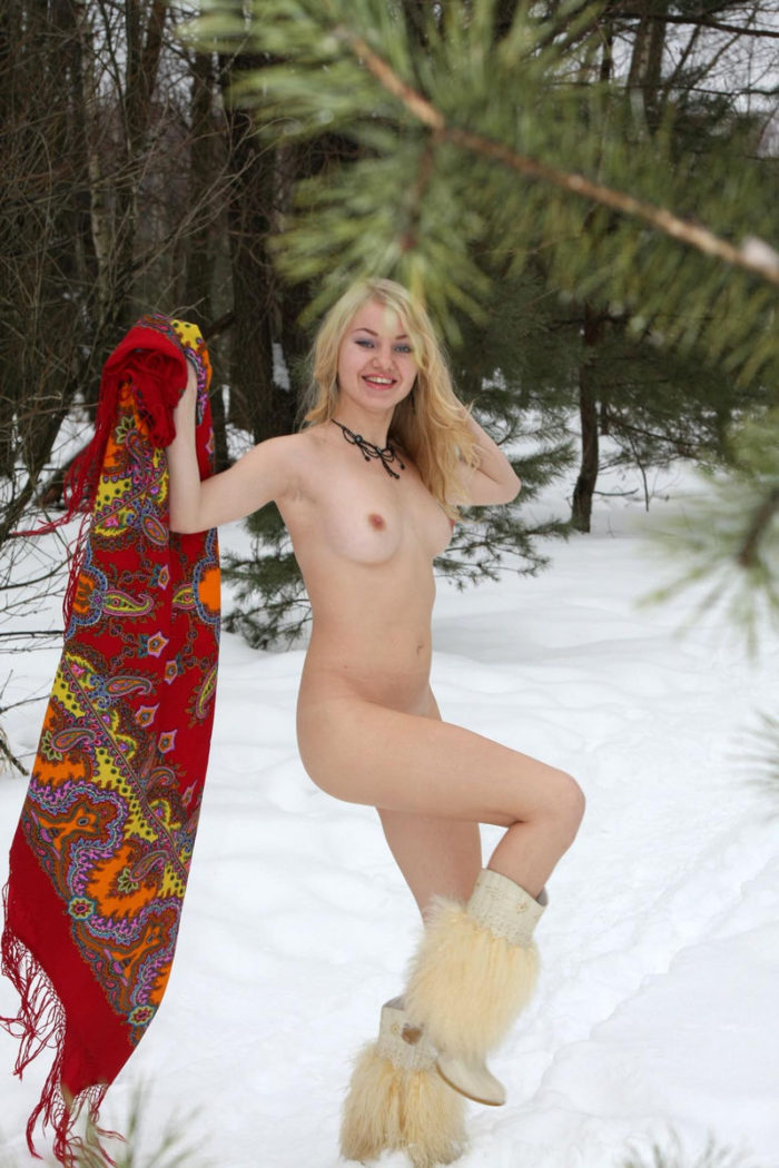 Smiling russian blonde plays with snow at forest