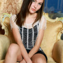 Sweet Belonika bares hr petite, nubile body and smooth pussy as she poses on the   chair.