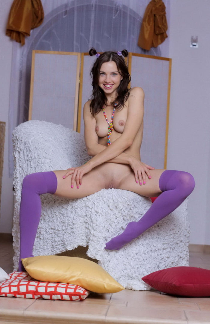 Teenage brunette in bright clothes reveals her assets with a smile