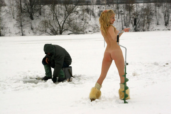 Young blonde helps fishermen at frozen river