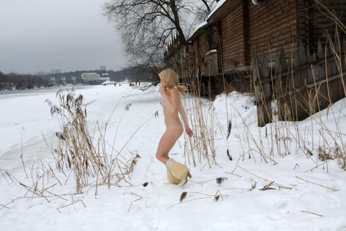 Young blonde without clothes on frozen river
