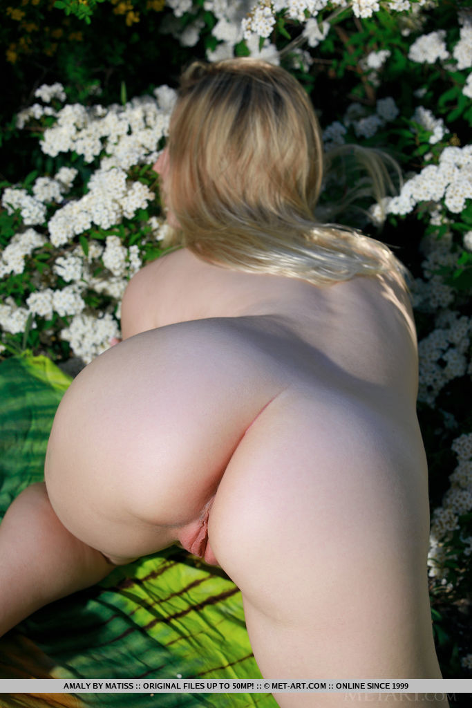 Amaly bares her gorgeous body and delectable pussy as she delightfully poses among the beautiful flowers.