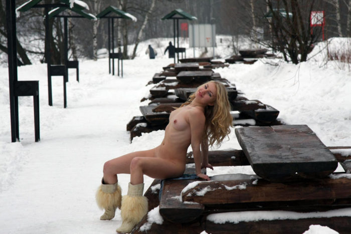 Blonde in boots clears snow in the park