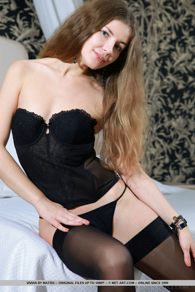 Blue-eyed cutie Vivian posing in a black bustier with matching string panty and knee-high stockings