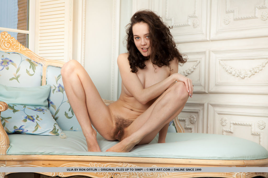 Curly-haired Ulia spreads her legs wide open on the bed baring her unshaven pussy and   slender body.