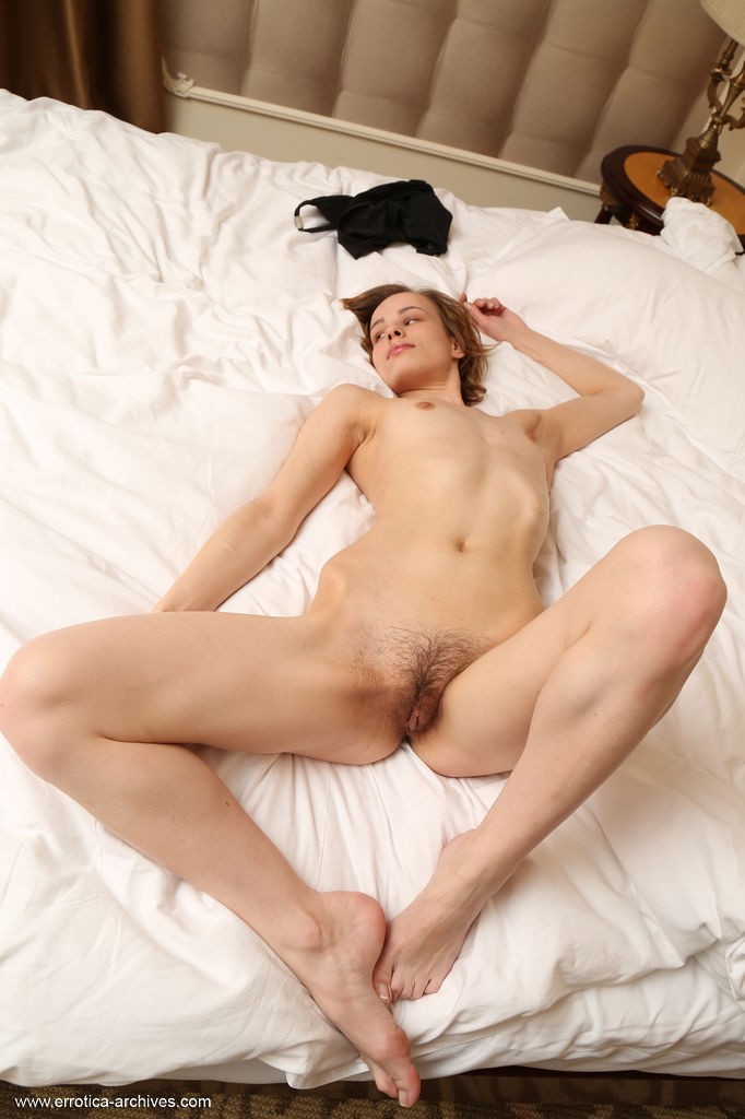 Liania sensually poses on the bed as she bares her petite body and hairy pussy.