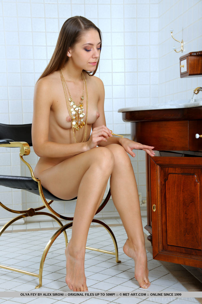 Olya Fey sensually poses on the chair as she spreads her legs wide open baring her sweet   pussy.
