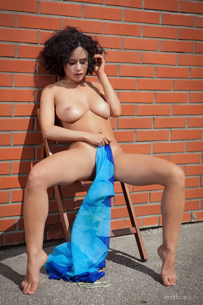 Pammie Lee bares her amazing physique with large breasts as she poses by the brick wall.