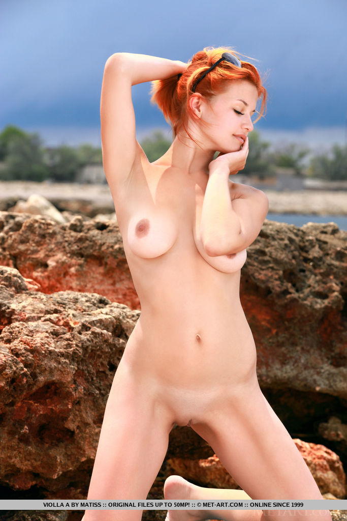 Redhead Violla A displays her gorgeous body and delectable pussy as she poses on the rocky shore.