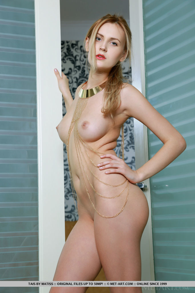 Tais bares her creamy, white body with pink, perky nipples and yummy pussy as she poses on the chair.