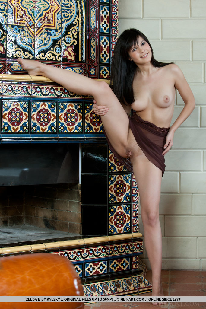 Zelda B's cheerful smile and soft, feminine curves stand out against the intricate details of the fireplace