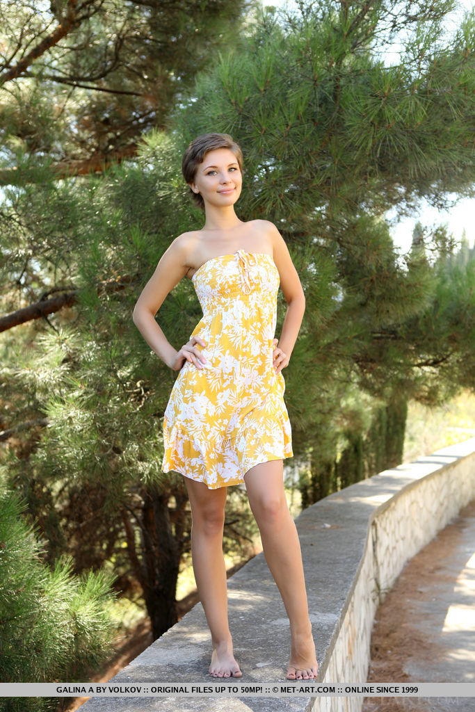 A playful Galina A lifts the hem of her dress to show off her shaved snatch