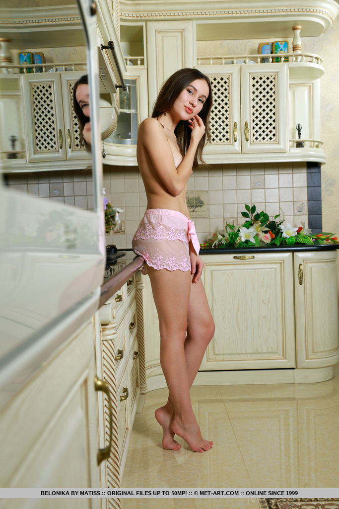 Belonika shows off her petite body with small tits and smooth pussy as she poses by the kitchen.