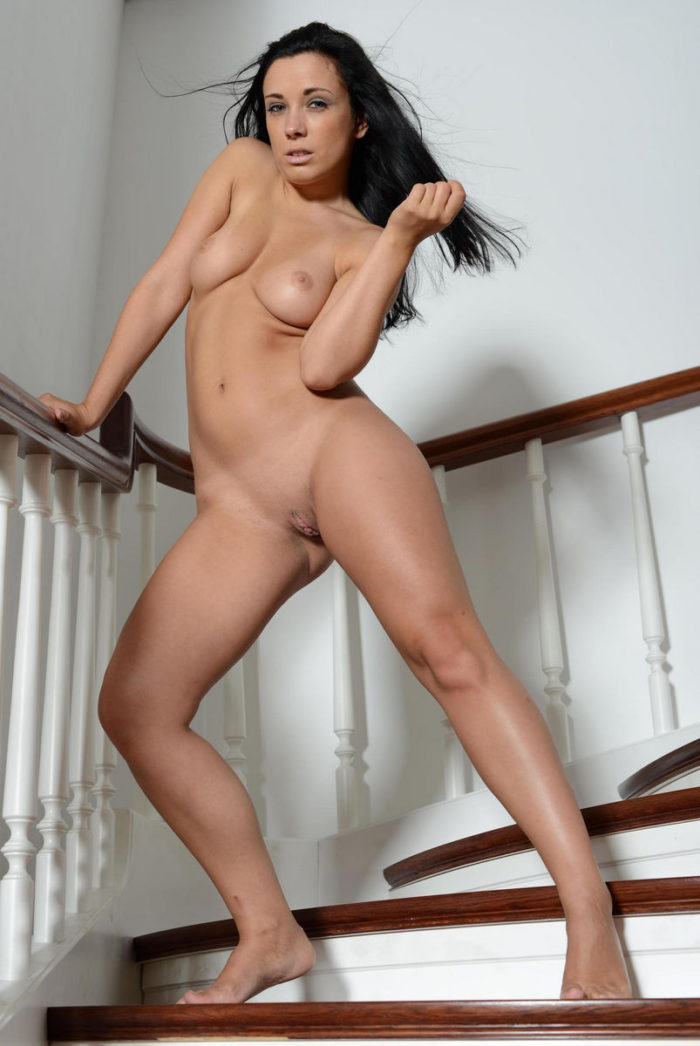 Busty brunette in sexy stockings on the staircase
