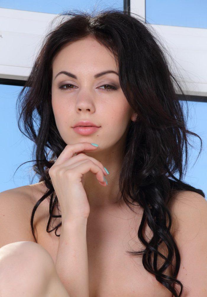 Curly brunette Genie with hot sporty body on windowsill