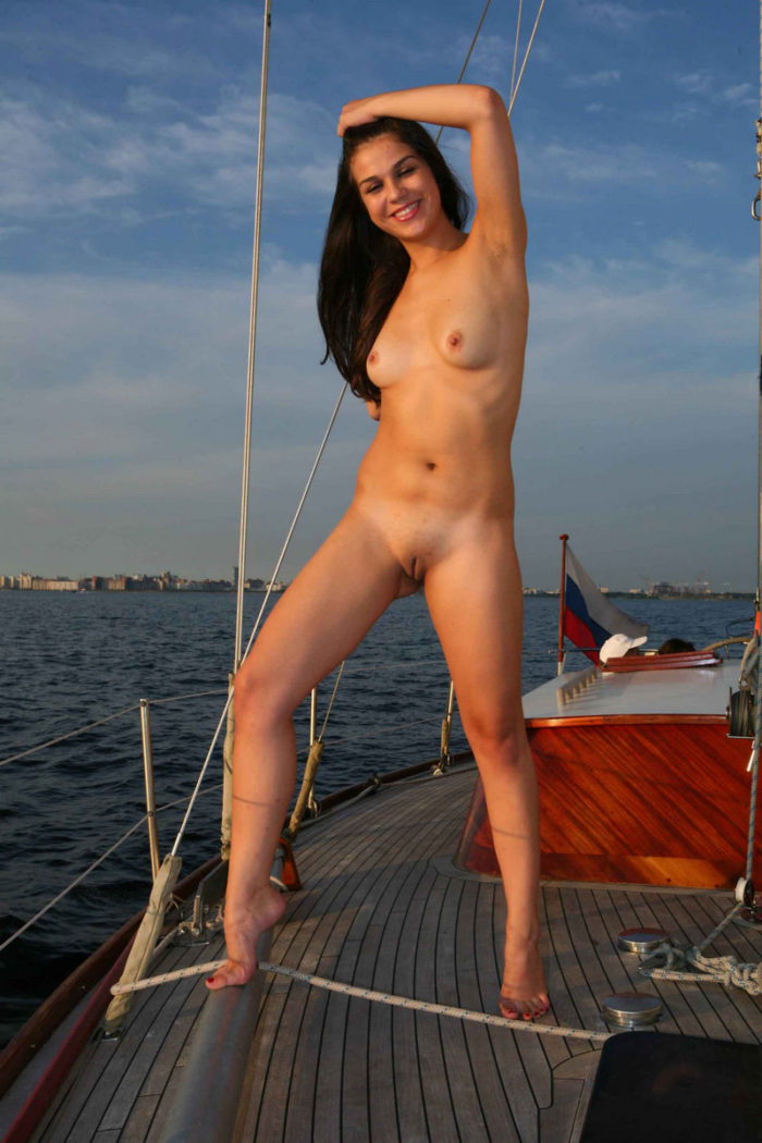 Naked brunette posing on yacht