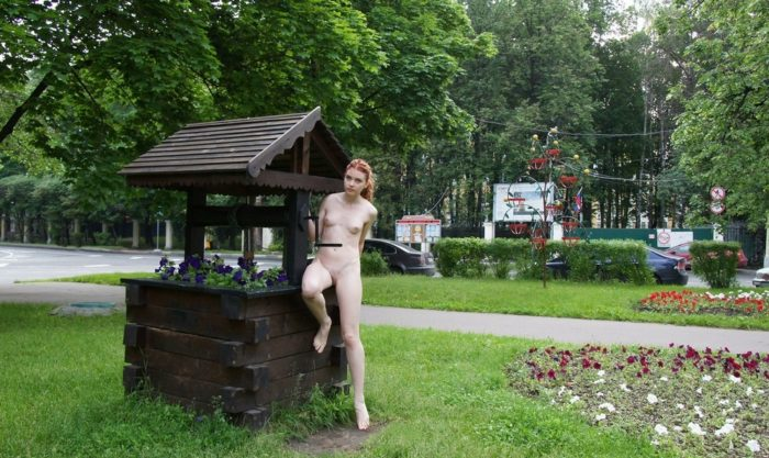 Naked teen Orabelle A at a flower bed outdoors