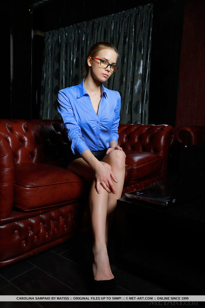 Newcomer Carolina Sampaio portrays a sexy secretary with her black-rimmed glasses, blue long-sleeved top, black leather skirt, and matching black stilettos