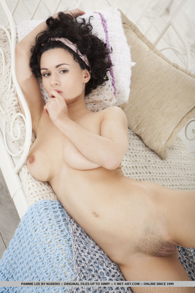 Pammie Lee displays her large puffy breasts and curvy body on the bed.