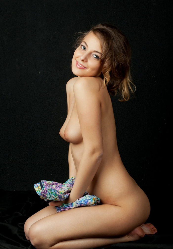 Smiling and naked Nikia A in black studio